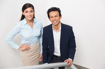 Uśmiechnięty człowiek biznesu i kobieta, stojąca na schodach