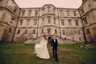 Uśmiechnięty nowożeńcy ze starożytnego zamku tle