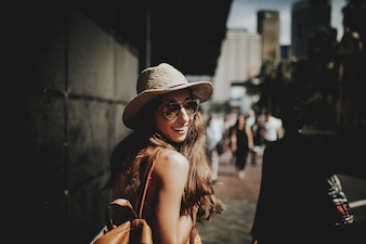 U? Miechni? Ta szcz ?? liwa kobieta spaceru w Sydney ulicy i obracaj? C si? Do spojrzenia na aparat.