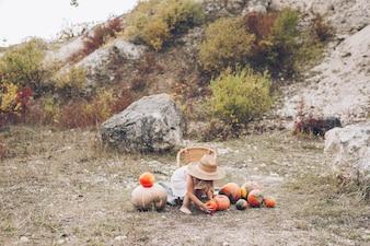 Urocza dziewczynka w słomkowym kapeluszu, wiklina krzesło, dynie, jesień