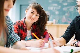 Wesoła dziewczyna siedzi z kolegami w tabeli