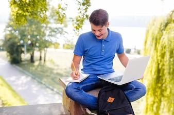 Wesoły chłopiec odrabianiu lekcji w parku