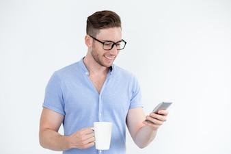 Wesoły inteligentny człowiek czyta wiadomość na telefonie