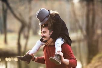 Wesoły mężczyzna z dziewczyną na ramionach