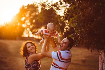 Wesoły rodzice trzymają swojego syna, stojącego na zewnątrz na drugim miejscu