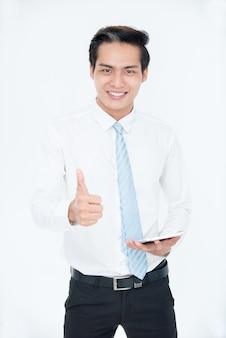 Wesoły udany azjatycki menedżer pokazujący kciuki do góry