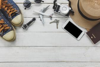 Widok z góry kobiety accessoires podróży concept.White telefon komórkowy, samolot, kapelusz, paszport, zegarek, okulary na drewnianym stole.