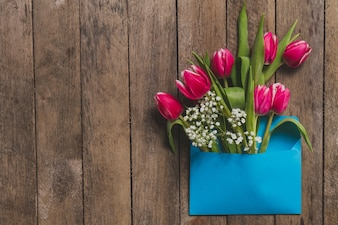 Widok z góry na niebieską kopertę z kwiatów na drewnianym stole