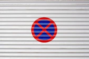 Zamknięte drzwi garażowe z zakazanym znakiem parkingowym na zewnątrz