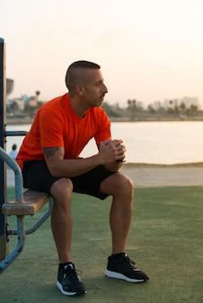 Zamyślony młody sportowiec siedzi na boisku