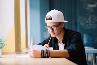 Zamyślony student pracuje nad zadaniami domowymi