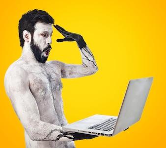 Zaskoczony prymitywny z laptopem na kolorowym tle