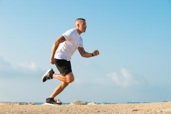 Zdeterminowany młody lekkoatleta biegnie na plaży