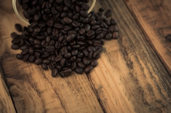 Ziarna kawy na drewnianym stole wychodzi z miską