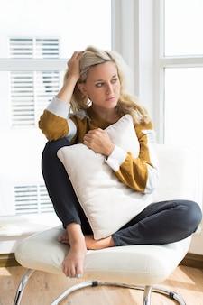 Zmartwiona młoda kobieta siedzi na krześle w domu