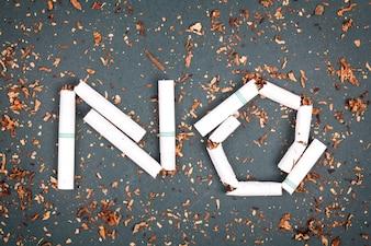 Znak zakazu palenia z łamanych papierosów i tytoniu na tablicy.