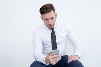 Zszokowany biznesmen czytania wiadomości na telefon