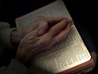 orando las manos sobre la Biblia