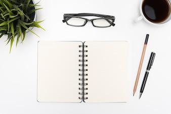 Abra el cuaderno espiral en blanco sobre el escritorio blanco