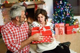 Abuelos junto a una caja de regalo en su sala de estar