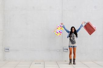 Adolescente feliz con las manos llenas de bolsas
