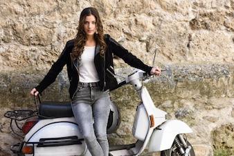 Adolescente guapa con una moto blanca