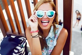 Adolescente llevando gafas de sol y poniendo cara graciosa