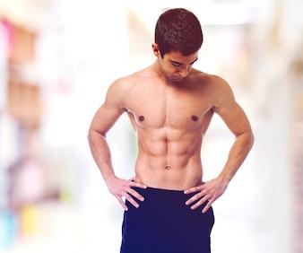 Adolescente sin camiseta mostrando su cuerpo