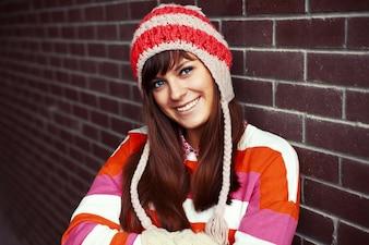 Adolescente sonriente posando mientras está de pie junto a una pared de ladrillo