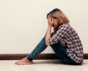 Adolescente triste con camisa de cuadros llorando