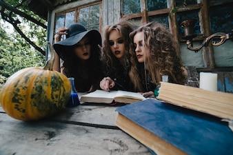 Adolescentes concentradas leyendo un libro de brujería