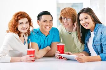 Adolescentes riendo con una tableta y algunas bebidas