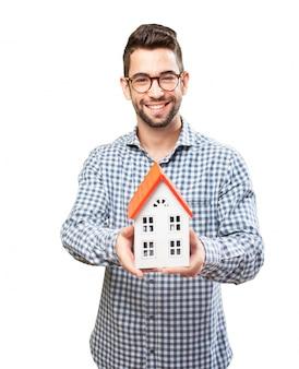 Adulto sonriente mostrando una casa de madera