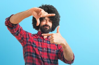 Afro hombre centrándose con sus dedos sobre fondo de colores