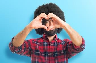 Afro hombre haciendo un corazón con las manos sobre fondo colorido