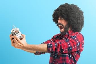 Afro hombre sosteniendo el reloj de la vendimia sobre fondo de colores