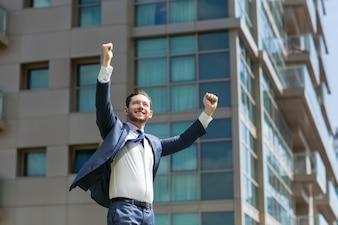 Alegre hombre de negocios celebrando el éxito al aire libre