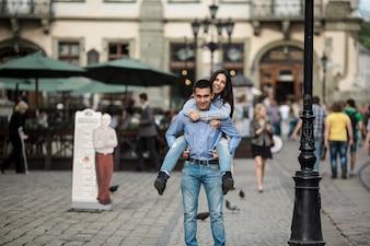 Alegre hombre sosteniendo a la niña en la espalda