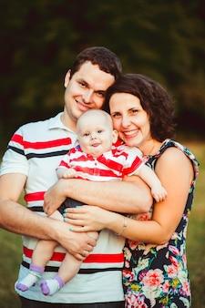 Alegres padres sonríen a un pequeño hijo en brazos