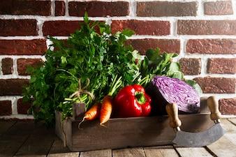 Alimento Fondo Colorido Vegetal. Sabrosas verduras frescas en caja de madera en la mesa de madera. Fondo De La Cocina. Espacio De La Copia.
