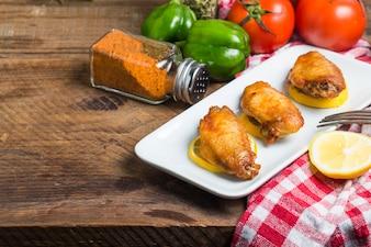 Alitas de pollo con verduras de fondo