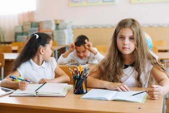 Alumnos sentados en los escritorios en el aula