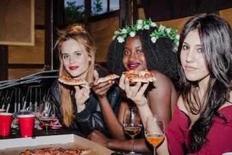 Amigas posando con pizza