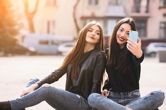 Amigas sentadas mientras se toman una foto