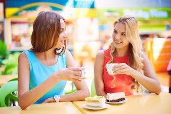 Amigas tomando una taza de té y un trozo de pastel