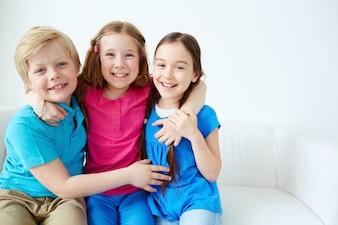 Amigos jóvenes abrazados en el sofá