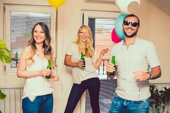 Amigos riéndose en la fiesta con botellas de cerveza