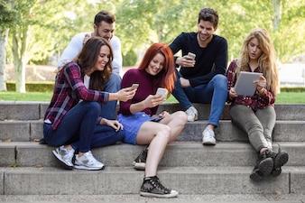 Amigos sentados en unas gradas con smartphones y tablets