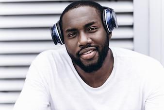 Apuesto hombre afroamericano vistiendo ropa casual en la ciudad moderna escuchando música con auriculares