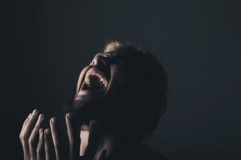Apuesto hombre de negocios gritando como loco, Stressed con el trabajo. Retrato del estudio contra el fondo negro.